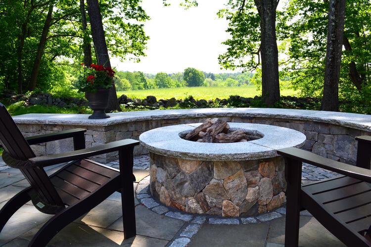 Natural stone fire pit featuring Woodbury Gray granite