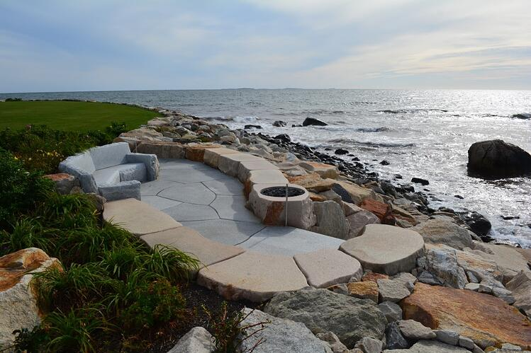 Oceanfront seating in Rye, NH. Woodbury Gray granite custom patio pavers and couch. Project by Great Works Landscape.