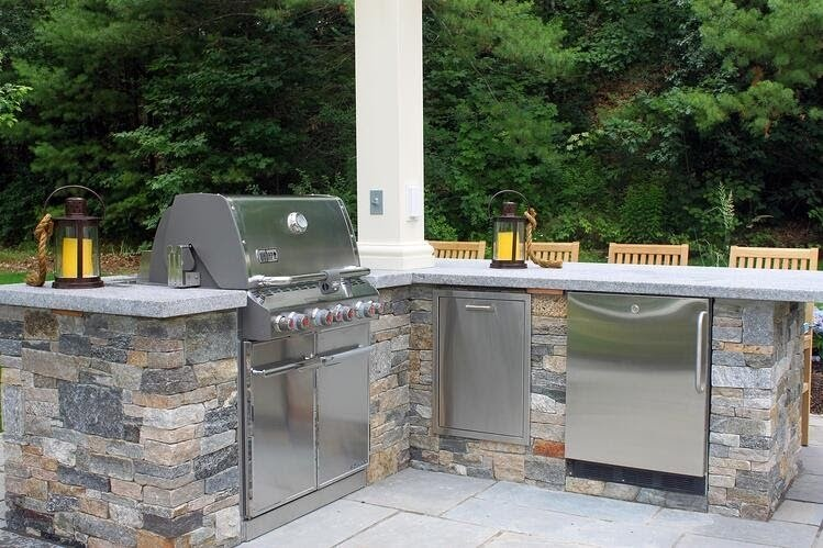 An outdoor kitchen crafted with Boston Blend Ledgestone thin veneer and Woodbury Gray granite walls caps and countertop. Project by Northern Lights Landscape.