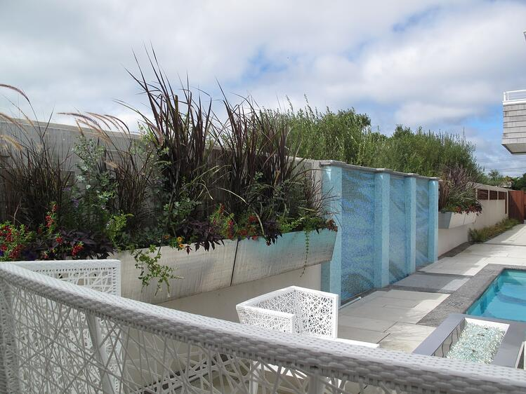 Caledonia granite was used as coping for the pool and water wall, as well as an edge around the entire patio. Project by Magma Design Group.