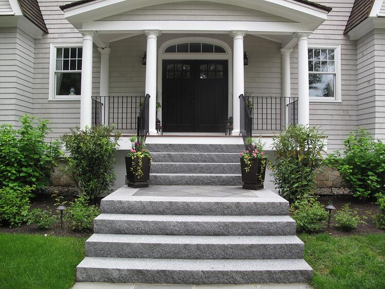 Woodbury Gray granite split face steps with bluestone on the landing. Project by Magma Design Group.