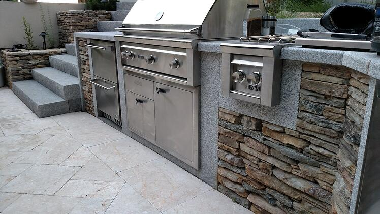 A fully functional outdoor kitchen with sandblasted Woodbury Gray granite countertops and locally-sourced fieldstone adds warmth and a natural aesthetic to this spacious Rhode Island backyard patio. Project by Magma Design Group.