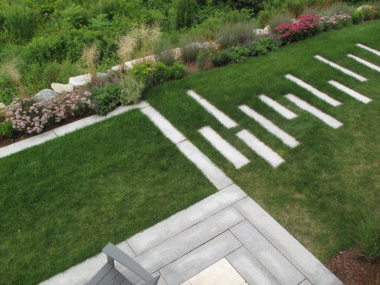 A minimalist patio design with Woodbury Gray granite pavers.
