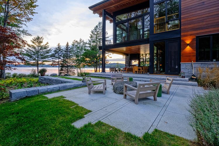 A two tiered Woodbury Gray granite patio and steps extend from this Lake Sunapee home. Project by Pellettieri Associates, designed with Joe Rolfe of Stone Mountain Masonry.