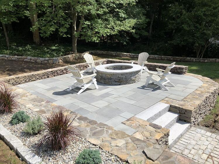 Patio and fire pit constructed of granite and natural stone. Project by MDM Construction Management.