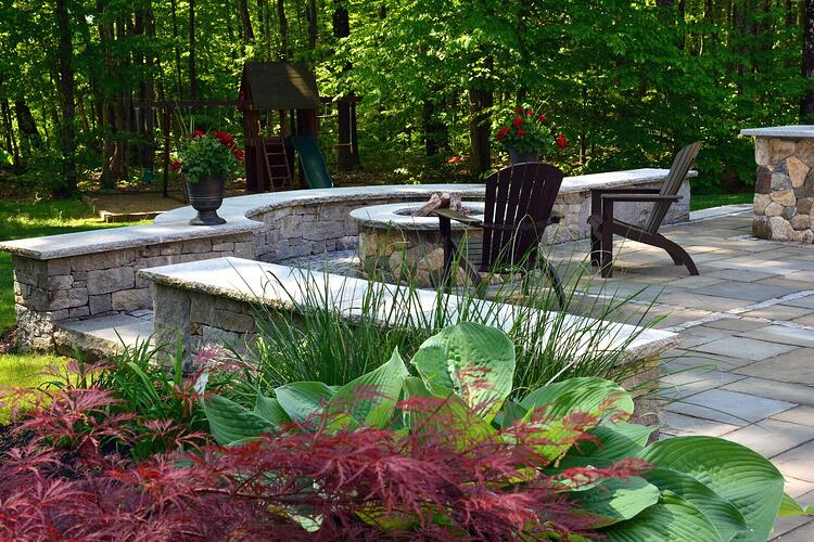 Patio and fire pit constructed of granite and natural stone. Project by Northern Lights Landscaping Contractors.
