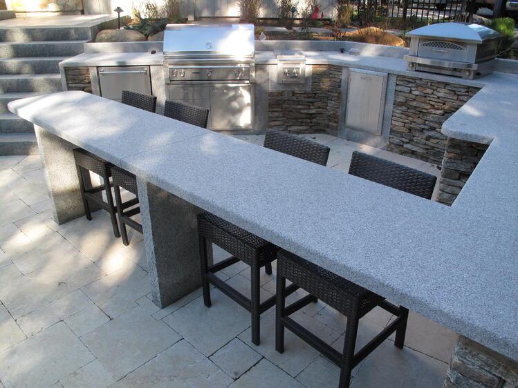 Outdoor kitchen and pool area featuring natural stone and granite. Project by Magma Design Group.