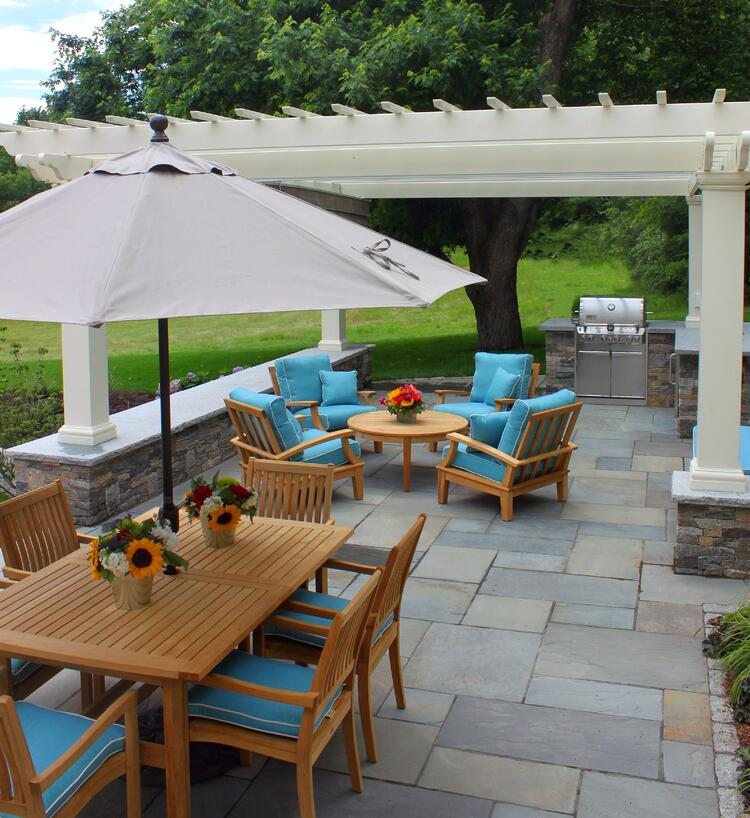 New Hampshire outdoor kitchen featuring natural stone and granite. Project by Northern Lights Landscape Contractors.