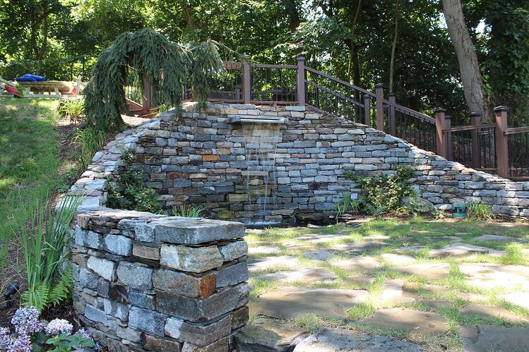 Woodbury Gray granite spillway on a weathered fieldstone wall. Project by See Level Landscape Design.