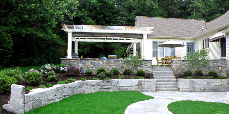 New Hampshire outdoor retreat with natural stone and granite. Project by Northern Lights Landscape Contractors.