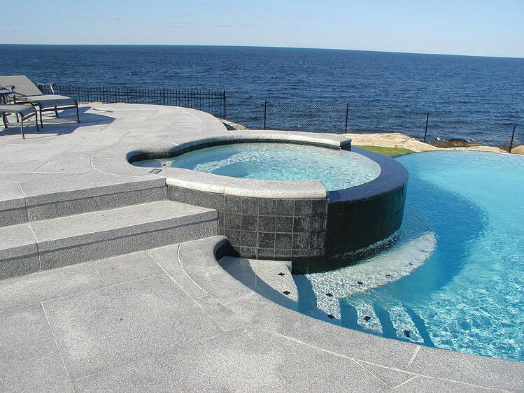 Woodbury Gray granite coping and decking spillover spa ocean view