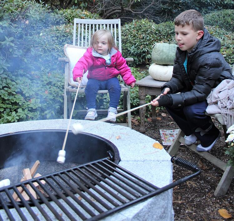 Roasting marshmallows over a DIY Woodbury Gray granite fire pit