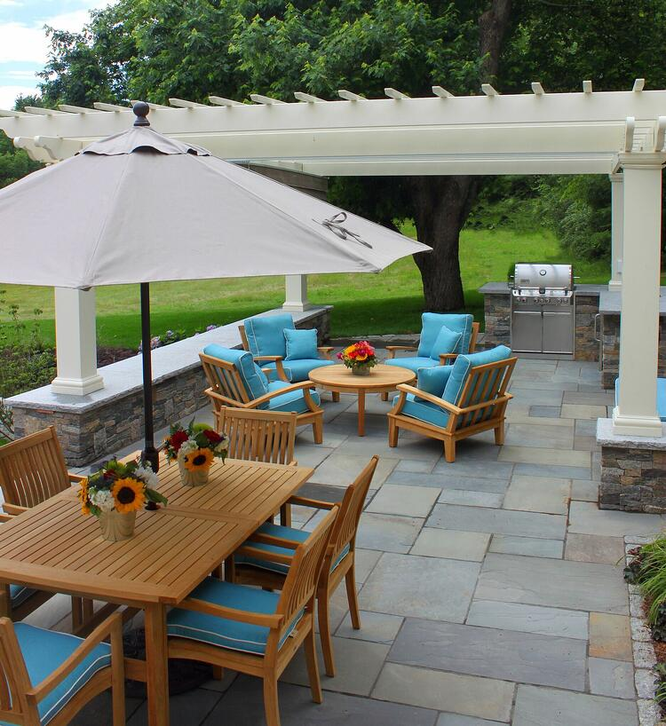 Outdoor dining area with bluestone patio and natural stone outdoor kitchen. Project by Northern Lights Landscape Contractors.