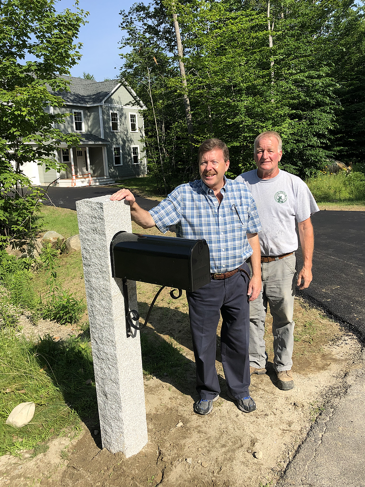 Swenson Granite Works crane truck operator and homeowner stand with newly installed granite mailbox post