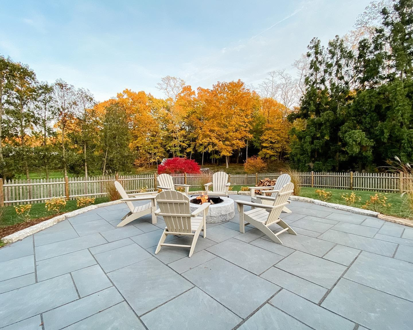 Round Woodbury Gray granite fire pit on patio with Adirondack chairs as fire pit seating gathered around fire pit creating a beautiful entertaining area for this family's outdoor living space