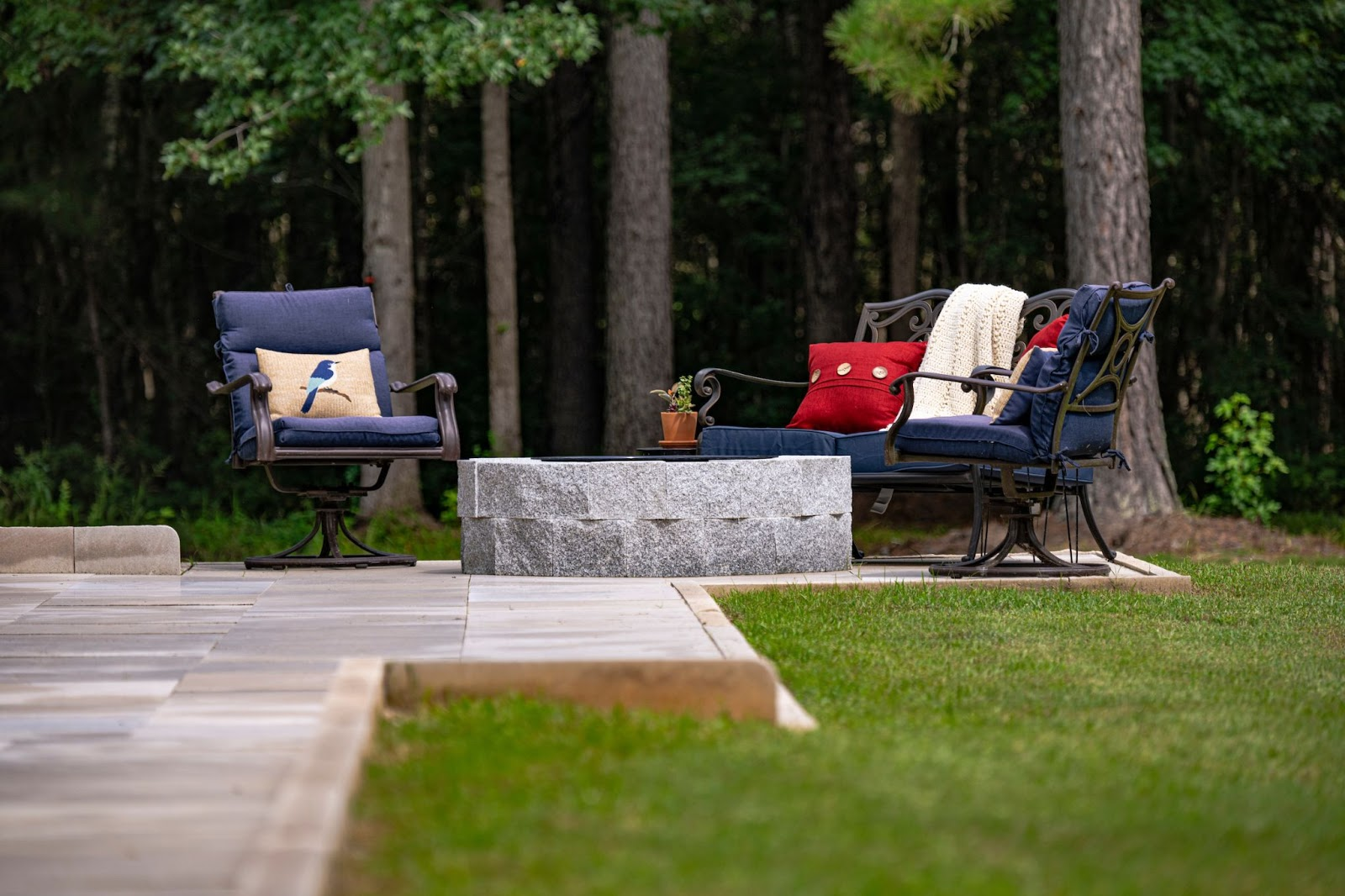 Granite fire pit with seating, Indiana Limestone patio, and summer decor