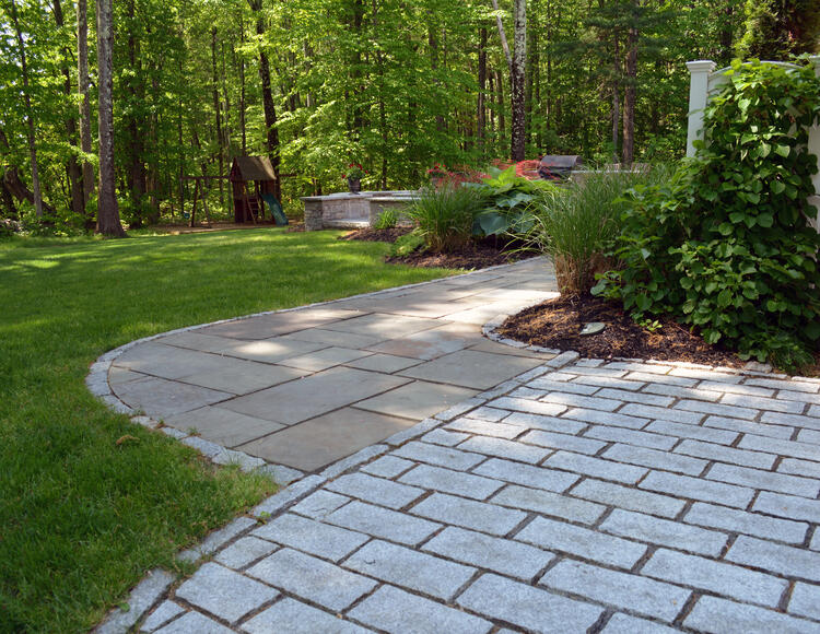 Standard granite cobbles provide an attractive separating border between these antique granite and full color bluestone patio areas.