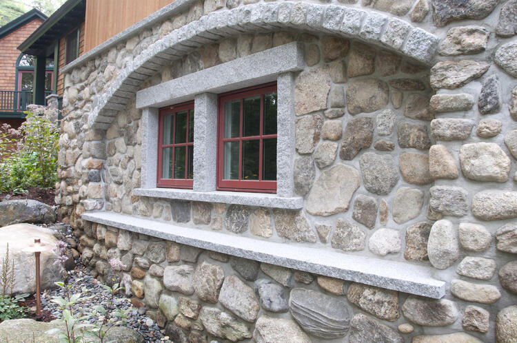 Tumbled Gray Cobblestone window archway on home exterior