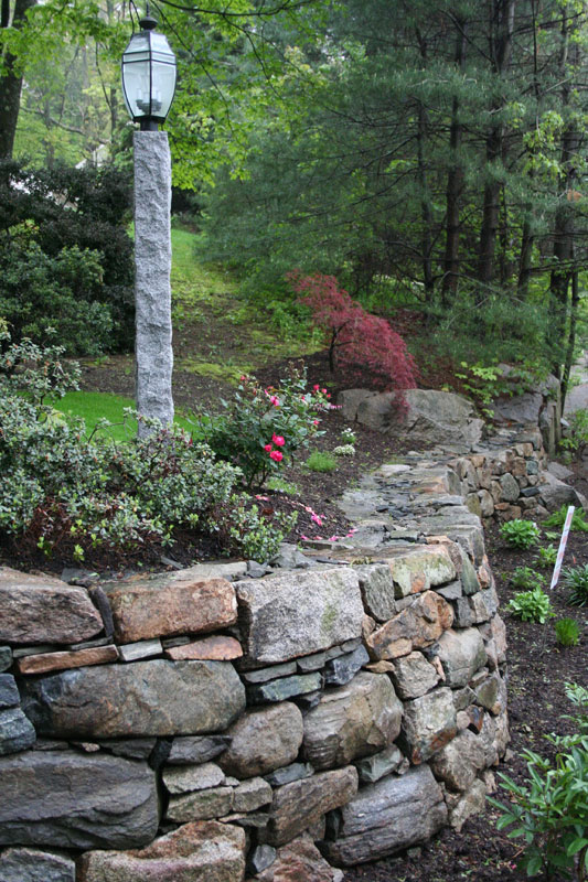 Woodbury Gray lamp post complements a natural stone retaining wall -- project by Ahronian Landscaping
