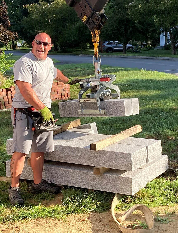 Swenson Granite Works Crane truck operator Doug Baillie gets ready to install a set of Woodbury Gray granite steps at a Concord, New Hampshire customer's home