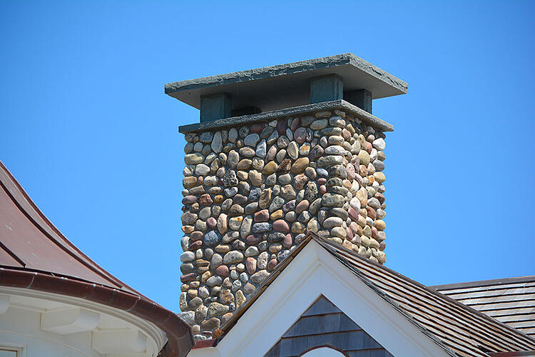 Stone veneer chimney with granite caps and supports