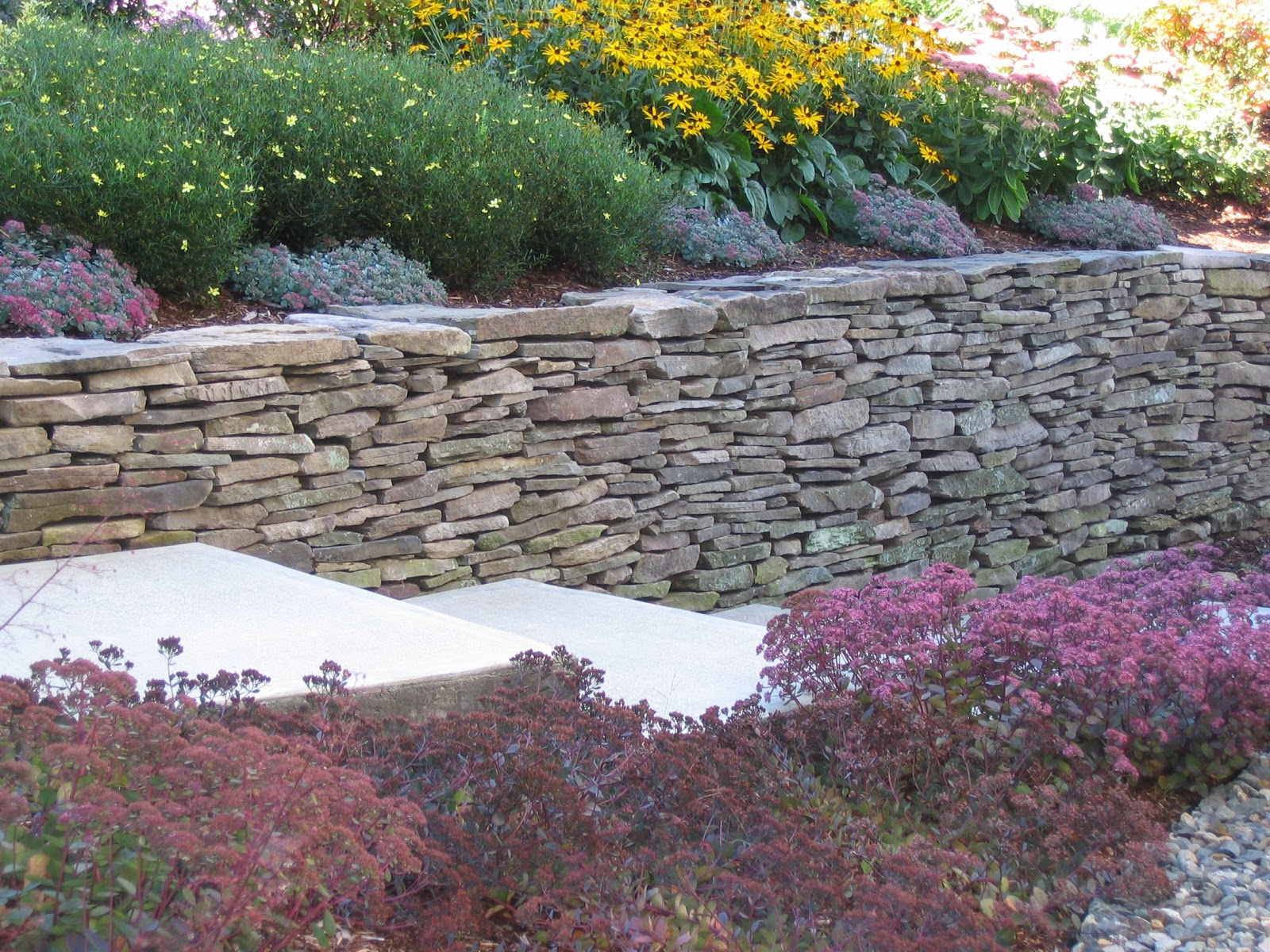 Thin weathered fieldstone retaining wall.