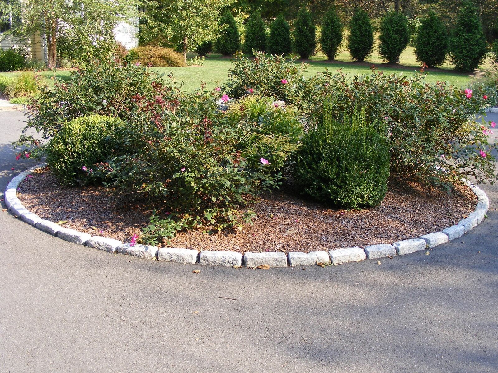 Standard granite cobblestones edge the planter bed in the center of a driveway